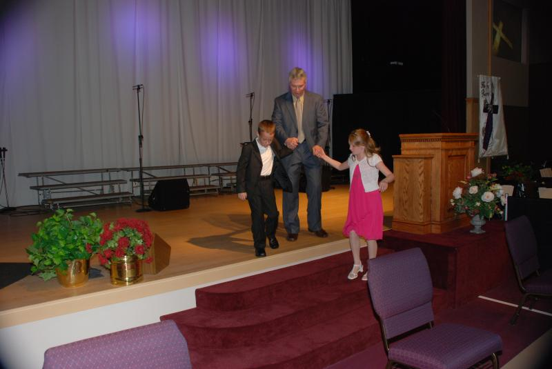 Dennis's grandchildren escort him off stage.